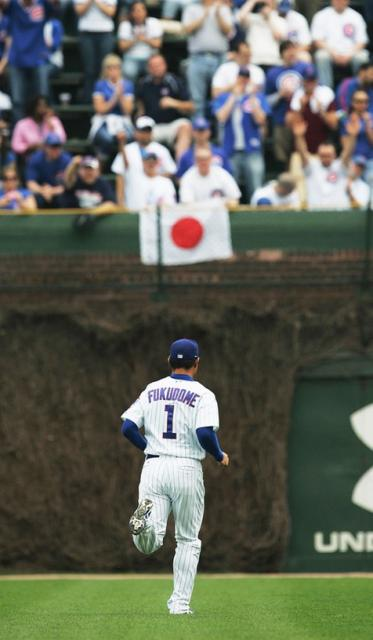 Fukudome runs to right field where a Japanese flag is hung by a fan.jpg