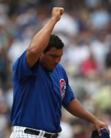 Carlos Zambrano removes his cap and raises his arm.jpg